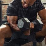 Muscular guy lifting dumbbell while sitting on bench at gym. Mat