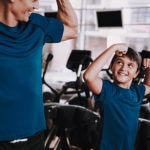 Young Father And Son Preparing For Training In Gym. Healthy Life