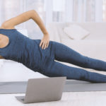 Happy Latin Woman Doing Side Plank Exercise While Watching Worko